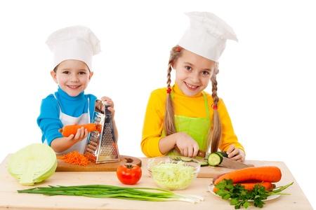niños cocinando: Dos niños hacer la ensalada, cocinar las verduras. Aislado en blanco
