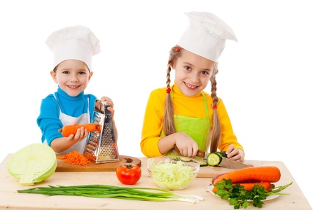 the grater: Two kids making salad, cooking the vegetables. Isolated on white
