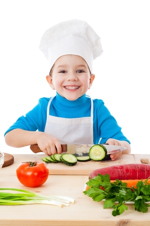 Little boy cutting the cucumber, isolated on white photo