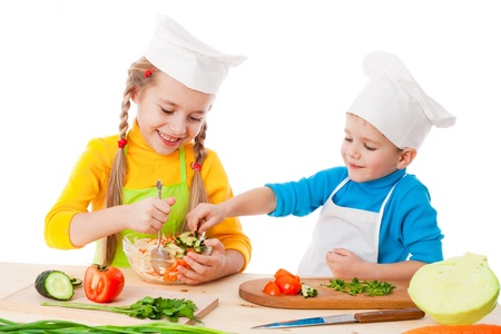 Two smiling kids mixing salad, isolated on white photo