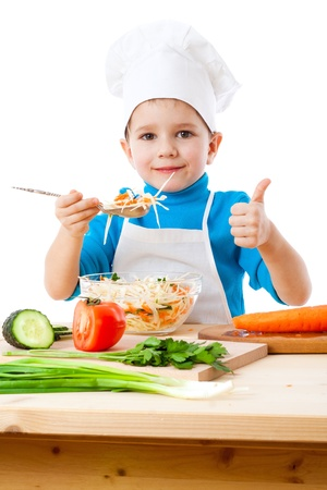 niños cocinando: Cocina pequeña con ensalada y el pulgar hacia arriba signo aislado en blanco Foto de archivo