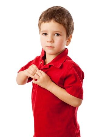 Serious kleiner Junge knöpft auf einem roten Hemd, isoliert auf weiß