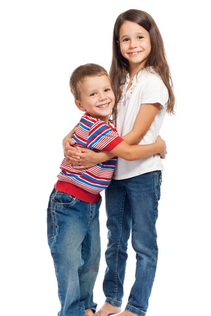 Two smiling little kids hugging each other, isolated on white