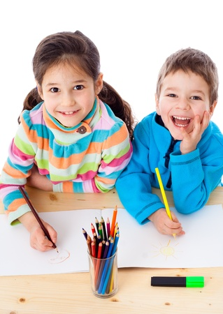 Two little kids at the table draw with crayons, isolated on white photo