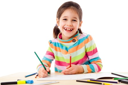 Smiling little girl at the table draw with crayons, isolated on white photo