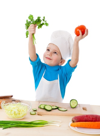 Little cook raising up hands with parsley and tomatoes, isolated on white