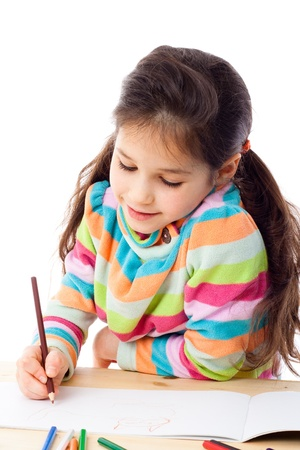 Smiling little girl at the table drawing the cat with crayons, isolated on white Stock Photo - 12353550
