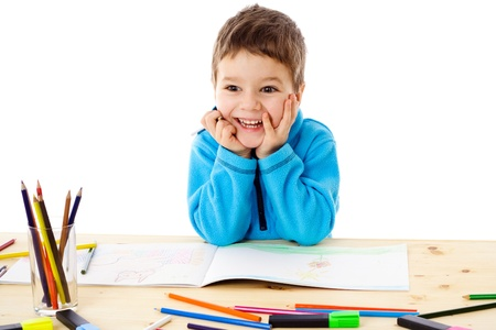 little table: Smiling little boy at the table draw with crayons, isolated on white Stock Photo