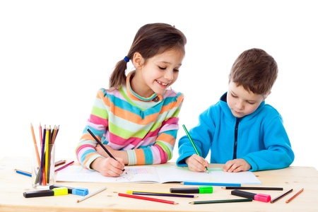 pry: Two little kids at the table draw with crayons, isolated on white