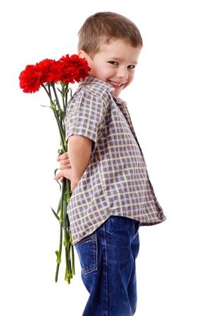 mamma e figlio: Ragazzo sorridente che nasconde un mazzo di garofani rossi dietro di s�, isolato su bianco