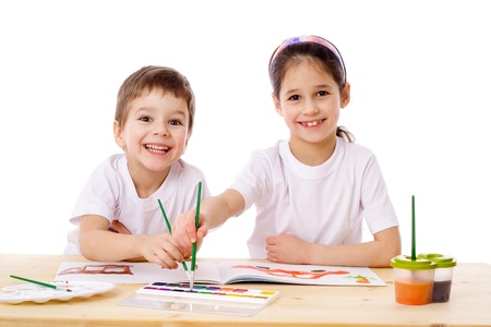 little table: Two smiling kids at the table draw with watercolor, isolated on white