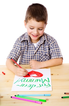 Smiling little boy at the table draw with crayons for mum, isolated on white Stock Photo - 12353561