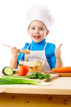 Little cook tasty salad and showing thumb up sign, isolated on white Stock Photo