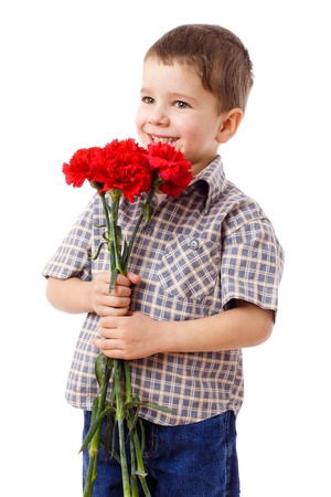 Smiling boy hiding a bouquet of red carnations, isolated on white