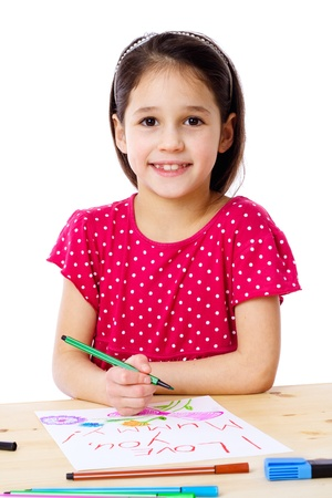 depict: Smiling little girl at the table draw with crayons for mum, isolated on white