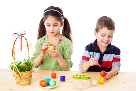 Two kids painting easter eggs, isolated on white photo