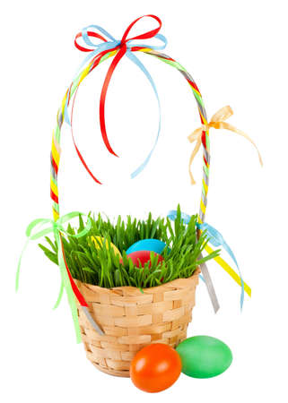 Easter eggs in basket with green grass, isolated on white photo