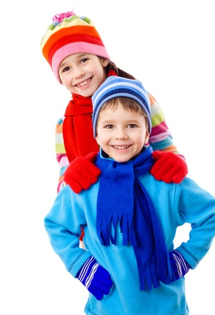 Two kids in winter clothes standing together, isolated on white photo
