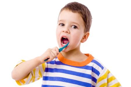 Little boy brushing teeth, isolated on white photo
