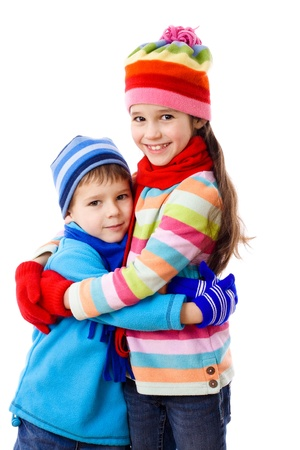 warm clothes: Two kids in winter clothes standing together, isolated on white