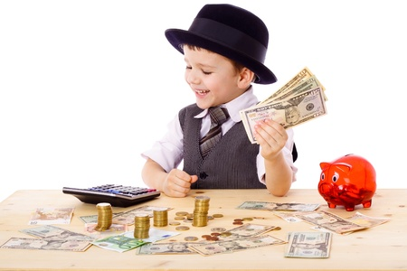 Little boy in black hat and tie at the table counts money, isolated on white