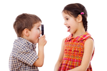 sticking tongue: Boy looks at girl with a magnifying glass, isolated on white