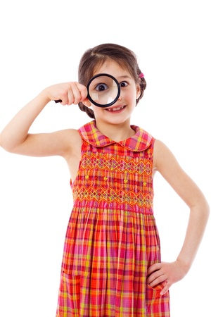 Smiling girl looking through a magnifying glass, isolated on white