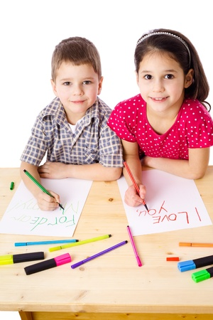 Two smiling kids at the table draw with crayons for mum, isolated on white Stock Photo - 12610980