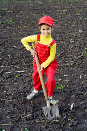 Little girl digs a big shovel in the field photo