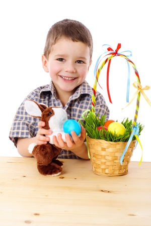 Smiling boy playing with easter eggs and bunny, isolated on white photo
