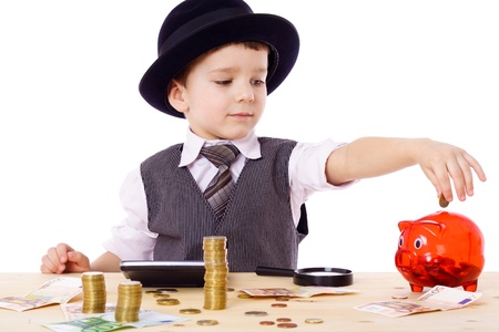Little boy like a boss at the table counts money, isolated on white photo