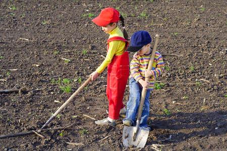 arando: Dos niños con las herramientas de jardinería en el campo