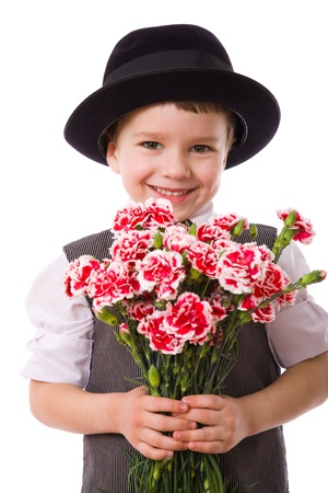 Happy boy standing with a bouquet of pink carnations, isolated on white photo
