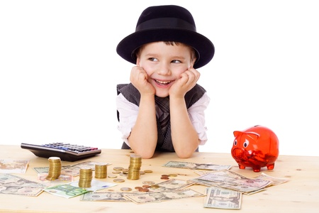 Happy boy in black hat and tie at the table with pile of money, isolated on white photo