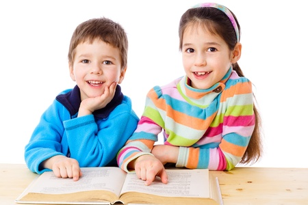 Two kids at the table reading the book, isolated on white Stock Photo - 12674922