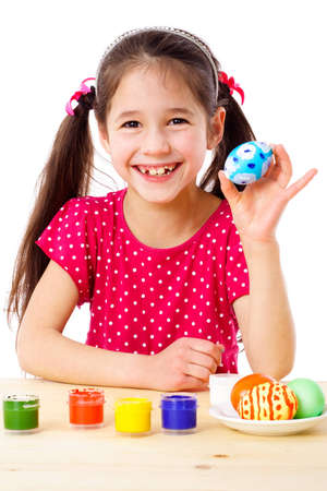 Happy girl showing painted easter egg, isolated on white photo