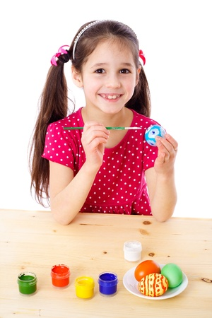 Smiling girl painting easter eggs, isolated on white photo