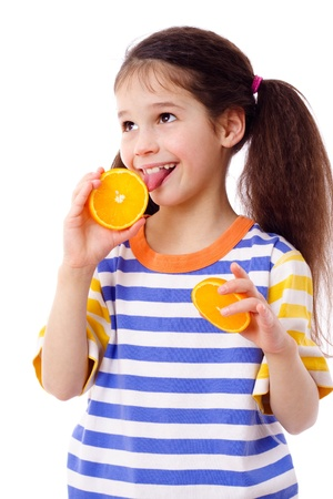 Happy girl tries to taste a slice of orange, isolated on white