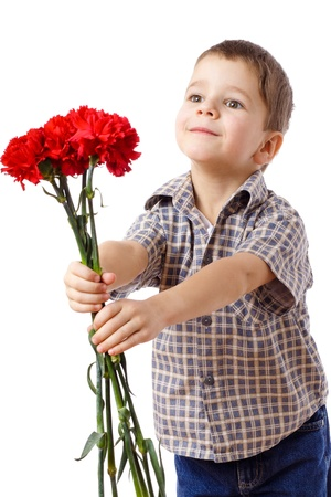 Smiling boy stretches forward a bouquet of red carnations, isolated on white