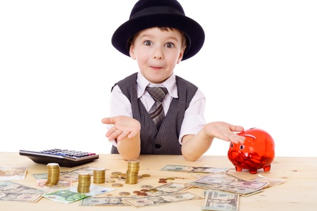 Sly boy in black hat with empty hands at the table with pile of money, isolated on white photo
