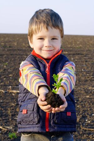 Little boy on field with plant in hands photo