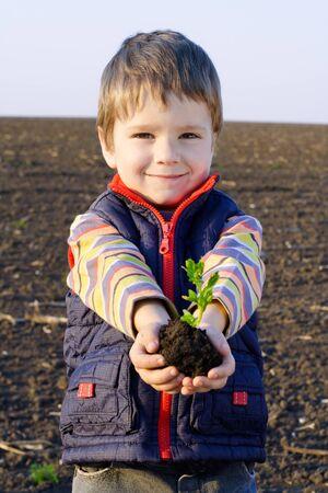 ni�os ayudando: Ni�o en el campo con la planta en las manos