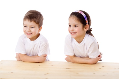 look right: Two smiling kids sitting at the empty table and looking aside, isolated on white