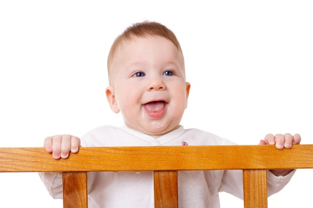 slobber: Smiling baby with slobber on face is standing in the bed, isolated on white