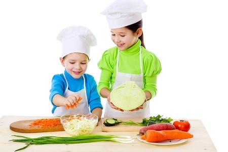 ni�os cocinando: Dos ni�os sonrientes preparaci�n de ensalada, aislado en blanco Foto de archivo