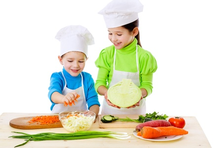child food: Two smiling kids preparing salad, isolated on white Stock Photo