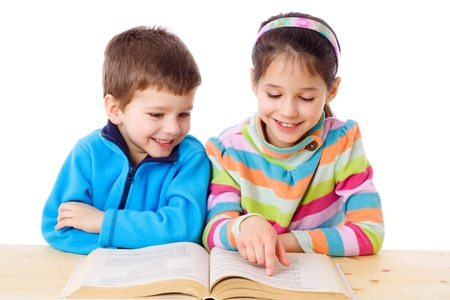 Two kids at the table reading the book, isolated on white Stock Photo - 13110319