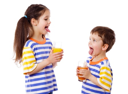Two funny kids with fruit juice and sticked out tongues, isolated on white photo