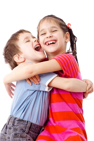 Two laughing funny kids standing together and embracing, isolated on white photo