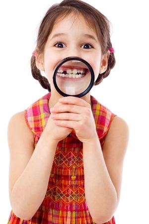 dentiste: Funny girl montrant les dents à travers une loupe, isolé sur blanc
